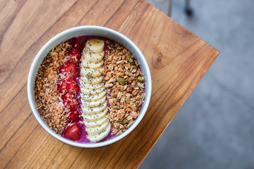 Overhead dragon fruit smoothie bowl with banana, strawberries, granola, coconut milk. Wooden table at coffee shop. Minimalist food photography