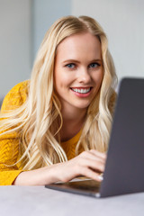 beautiful young blonde woman using laptop and smiling at camera