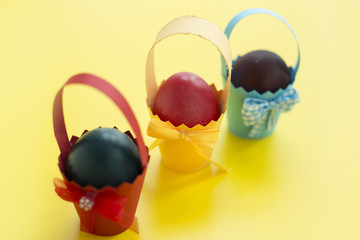 Colorful eastern eggs warped in paper cups. Selective focus