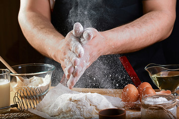 Baker sprinkle the dough with flour bread, pizza or pie recipe ingredients with hands, food on kitchen table background, working with milk, yeast, flour, eggs, sugar pastry or bakery cooking, set