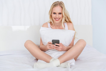 beautiful young woman holding smartphone and smiling at camera while sitting on bed