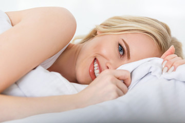beautiful blonde girl lying in bed and smiling at camera