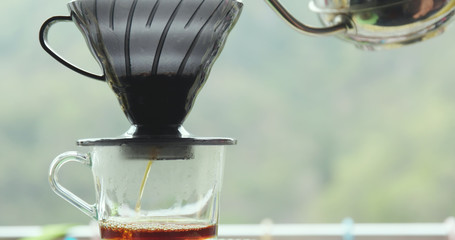 Making drip coffee over green background