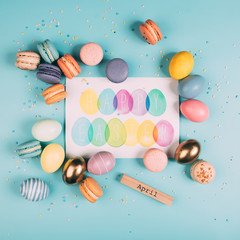 top view of easter eggs and macarons around happy easter greeting card on blue surface