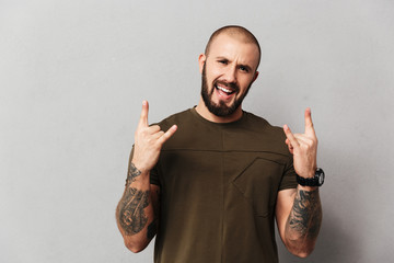 Image of cheerful hairless guy with beard and mustache smiling and showing rock sign, isolated over gray background Wall mural