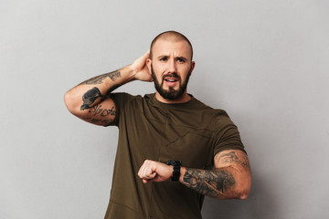 Portrait of good-looking man in casual t-shirt standing with watch on wrist and being late, isolated over gray background