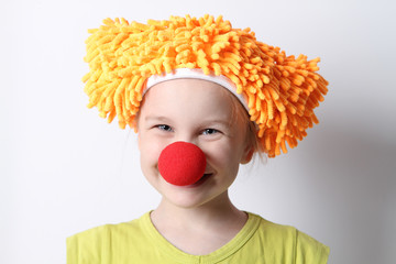 clown baby girl with a red nose in a funny cap