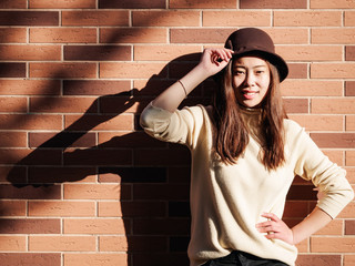 Outdoor portrait of young beautiful fashionable playful Chinese lady standing with her shadows on wall. Model wearing stylish hat & clothes. Sunny day. Female fashion. City lifestyle.