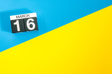 March 16th. Day 16 of march month, calendar on blue and yellow background flat lay, top view. Spring time. Empty space for text