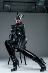 Kinky woman in sexy costume posing on chair on grey background