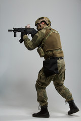 Full-length picture of aiming military man with gun