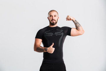 Image of well-built guy in black sporty clothing demonstrating bicep and gesturing thumb up, isolated over white background