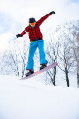 Image of athlete with snowboard jumping in snowy resort