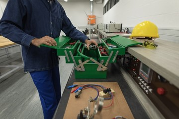 Male worker removing tools from toolbox