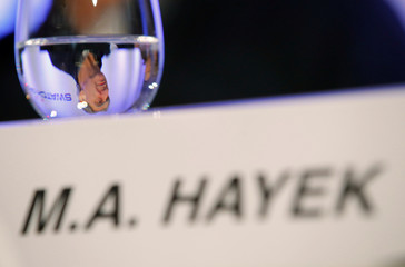 CEO and Chairman of the Board of the Swatch Group Hayek  is seen through a glass during the news conference in Biel