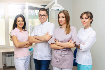 Cheerful group of young dentists and their assistants standing in the dental office and looking at camera and friendly smiling at white background of medical room.
