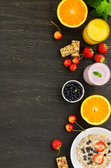 Healthy breakfast of muesli, berries with yogurt and orange juice on dark background.