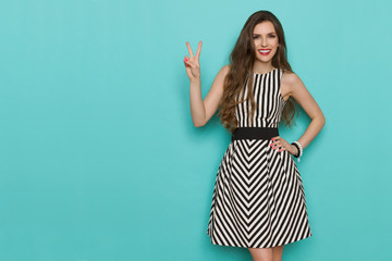 Smiling Beautiful Young Woman In Striped Dress Showing Peace Hand Sign