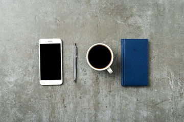 Office desktop with pen, smart phone and notebook