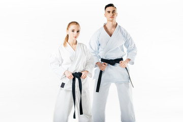 karate fighters holding black belts and looking at camera isolated on white