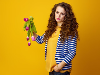 unhappy woman against yellow background showing wilted flowers
