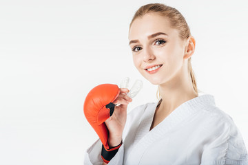 smiling female karate fighter holding mouthguard isolated on white