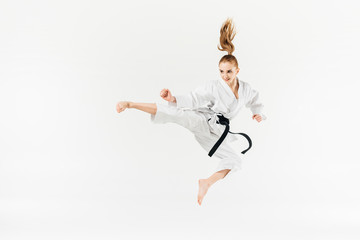 female karate fighter jumping and performing kick isolated on white