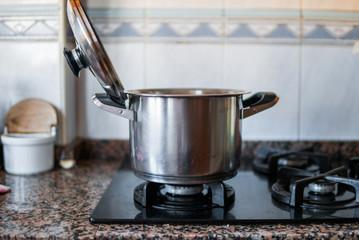Fotografía de una olla de plata en los fogones de una cocina de casa.