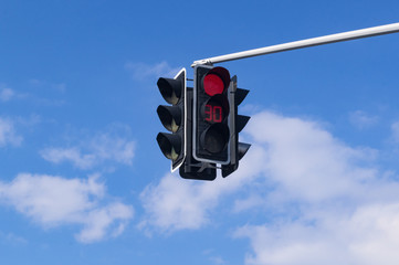 Traffic light with red light signal on sky background