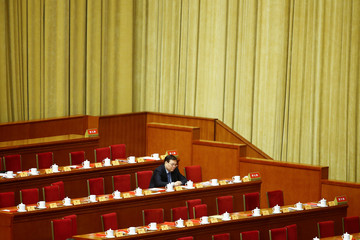 A lone delegate sits in his seat during a break in a plenary session of the Chinese People's Political Consultative Conference (CPPCC) at the Great Hall of the People in Beijing