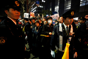 Police officers try to control protesters during a rally denouncing Japanese Prime Minister Shinzo Abe and Finance Minister Taro Aso in Tokyo