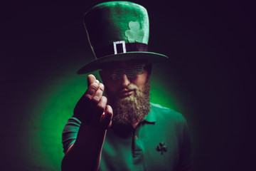 bearded young man in green irish hat and funny eyeglasses gesturing at camera