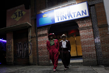 """Jesus Gonzalez de la Rosa and Arellano Diaz wear their """"Pachuco"""" outfits while posing for a photograph outside a dance hall named after late Mexican Pachuco Tin Tan, in Mexico City"""