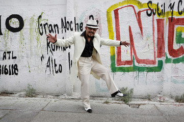 "Guardarrama Tapia wears his ""Pachuco"" outfit while posing for a photograph next to a wall with graffiti in Mexico City"