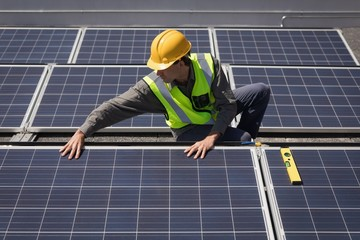 Male worker working on solar panels at solar station