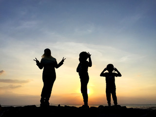 Silhouette of young mother and sibling playing together at the beach on sunset