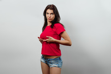 Young, beautiful girl, stands holding her breasts with her hands. Isolated on a light background. Different human emotions, feelings of facial expression, attitude, perception, body language.