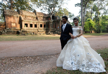 Newly married bride and groom take a picture at the Angkor Wat temple complex in Siem Reap