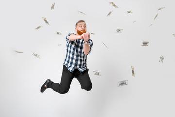 man standing under money rain