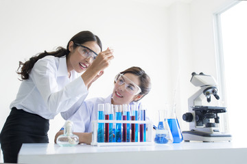 Beautiful asian health care researchers working in life science laboratory. Young female research scientist analyzing microscope slides in research lab