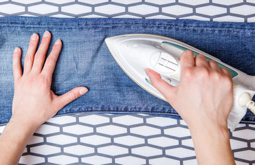 Picture of man ironing blue jeans on board
