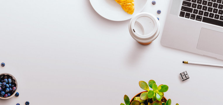 Desktop flatlay scene with MacBook, green plant, coffee cup, breakfast and stationery items, on a white background. Central negative space, banner shape.