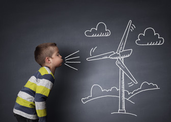 Child blowing a chalk wind turbine