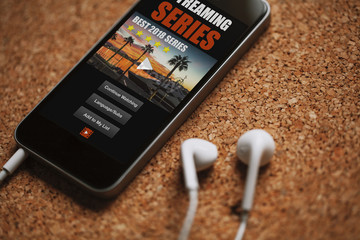 Streaming series app in a mobile phone screen, close to white earphones on a brown table.