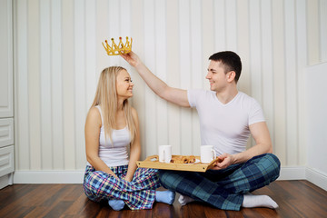 A happy couple in pajamas sit on the floor in a room against a striped wall background.