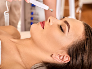 Electronic facial lift massage at beauty salon. Electric stimulation skin care of woman. Improvement of skin condition. Anti aging rejuvenation and non surgical treatment.