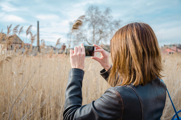 Young brunette woman taking photo in bulrush in nature with her phone, wearing leather jacket