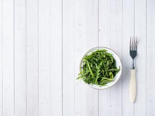 Dietary salad of arugula leaves in plate and white background