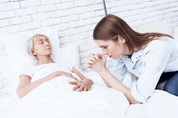 Girl is nursing elderly woman at home. Woman is feeling bad, girl is praying.