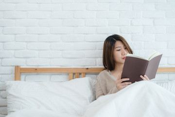 Lifestyle happy young Asian woman enjoying lying on the bed reading book pleasure in casual clothing at home. Relaxing lifestyle woman concept.